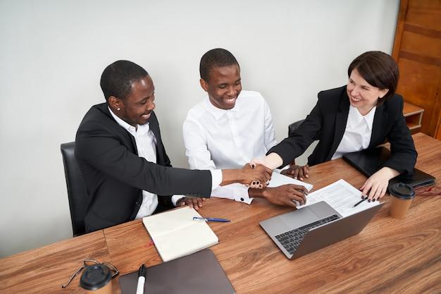 Junge glückliche geschäftsleute, die zusammen im modernen büro arbeiten, multiethnische teamarbeit, handshake-konzept
