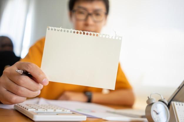 Junge glückliche geschäftsmannhand, die leeres papier mit kopienraum hält