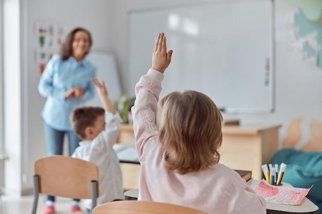 Junge glückliche grundschüler im hellen modernen klassenzimmer erheben ihre hände auf eine lektion