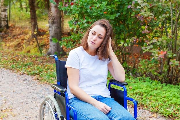 Junge glückliche handicap-frau im rollstuhl auf der straße im krankenhauspark, der auf patientendienste wartet. gelähmtes mädchen im ungültigen stuhl für behinderte menschen im freien in der natur. rehabilitationskonzept.