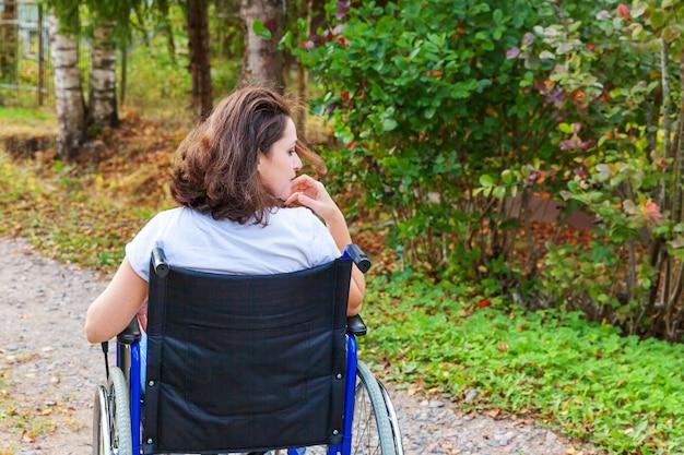 Junge glückliche handicapfrau im rollstuhl auf straße im krankenhauspark, der freiheit genießt