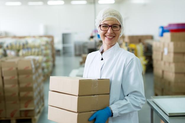 Junge glückliche hart arbeitende arbeiterin, die einen stapel kisten im fabriklagerraum trägt.