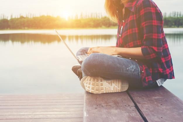 Junge glückliche hipster frau arbeitet mit ihrem laptop auf kuchen sitzen