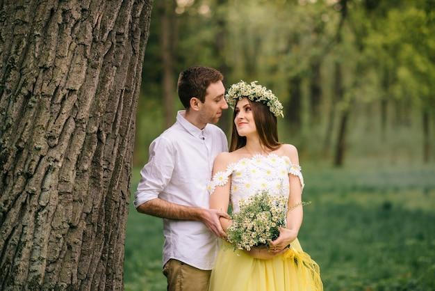 Junge glückliche jungvermählten, die in einem frühlingspark umarmen