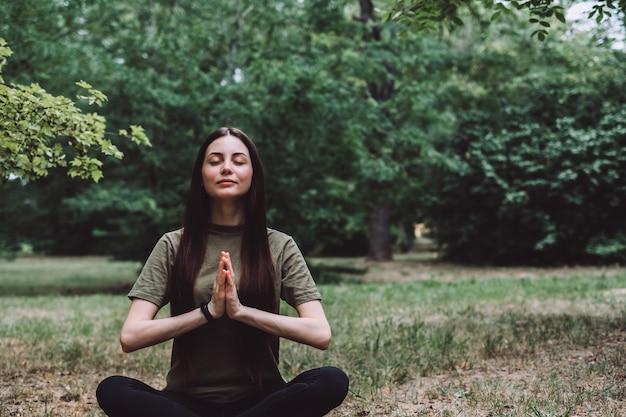 Junge glückliche kaukasische frau, die allein in der natur meditiert. gesunder lebensstil und entspannung.