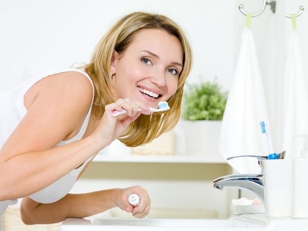 Junge glückliche kaukasische frau, die zähne mit zahnbürste im badezimmer reinigt