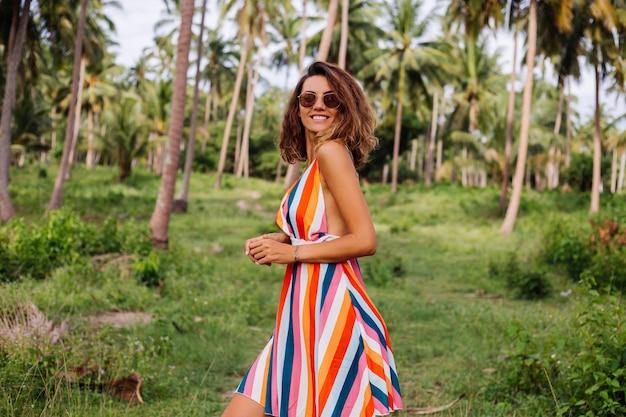 Junge glückliche kaukasische frau im bunten gestreiften sommerkleid mit dem kurzen lockigen haar im sonnenbrillenurlaub im warmen exotischen land.