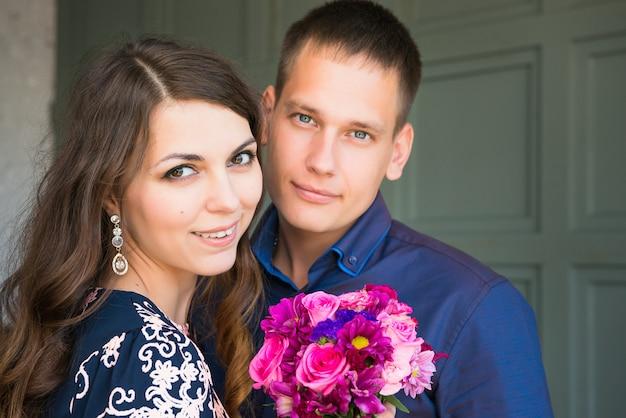 Junge glückliche kaukasische paarjungvermählten, die kamera betrachten