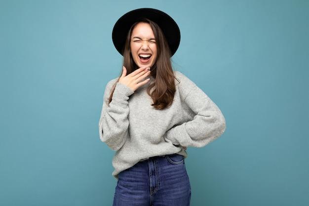 Junge glückliche lachende fröhliche lustige schöne brunetfrau modische dame in lässigem grauem pullover und