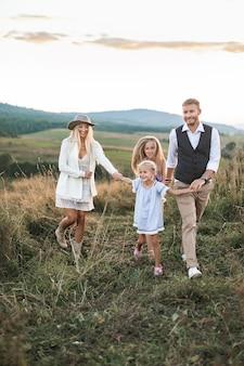 Junge glückliche lächelnde familie mit zwei töchtern, die spaß auf dem land haben