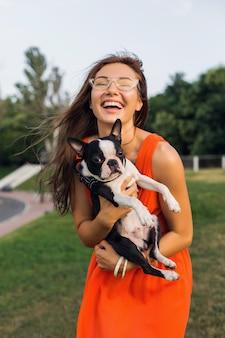 Junge glückliche lächelnde frau, die boston terrier hund im park hält, sonniger sommertag, fröhliche stimmung, spielend mit haustier, umarmungen, tragendes orange kleid, sonnenbrille, sommerart
