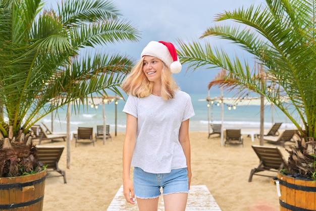 Junge glückliche lächelnde frau, die entlang strand in der weihnachtsmannmütze geht