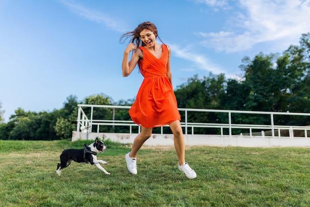 Junge glückliche lächelnde frau im orangefarbenen kleid, das spaß beim spielen mit hund im park, sommerart, fröhliche stimmung spielt
