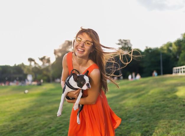 Junge glückliche lächelnde frau im orangefarbenen kleid, das spaß hat, mit hund im park, sommerart, fröhliche stimmung zu spielen