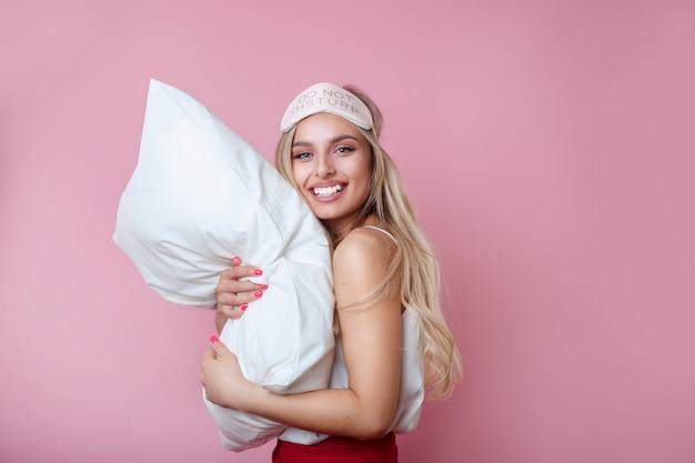 Junge glückliche lächelnde frau in den pyjamas, die orthopädisches kissen auf rosa wand halten.