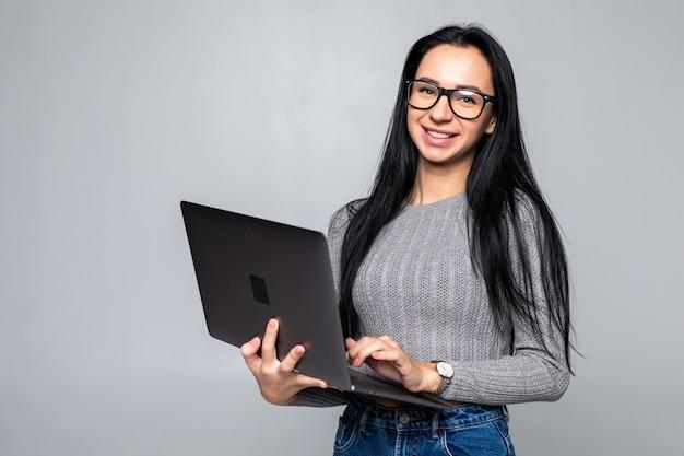 Junge glückliche lächelnde frau in der freizeitkleidung, die laptop lokalisiert auf grauer wand hält