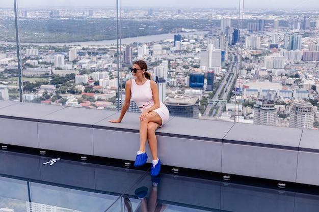 Junge glückliche lächelnde kaukasische frau reisende im passenden kleid und in der sonnenbrille auf hohem boden in bangkok