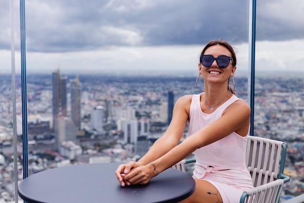 Junge glückliche lächelnde kaukasische frau reisende in passendem kleid und sonnenbrille auf hohem boden in bangkok stilvolle frau, die erstaunliche großstadtansicht erkundet