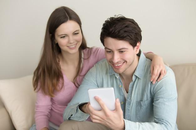 Junge glückliche lächelnde paare unter verwendung der tablette, videoanruf, online-shop