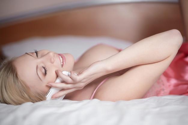 Junge glückliche lächelnde schöne frau, die auf bett liegt und am telefon spricht