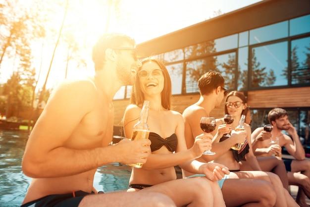 Junge glückliche leute, die zusammen am poolside sitzen.