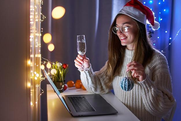 Junge glückliche lustige freudige frau, die weihnachtsmannhut trinkt champagner trägt