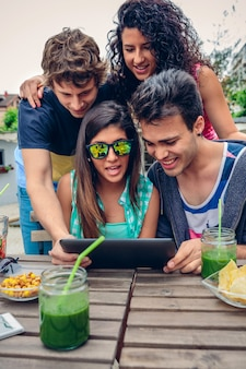 Junge glückliche menschen, die an einem sommertag im freien eine elektronische tablette mit gesunden getränken suchen. lifestyle-konzept der jungen leute.
