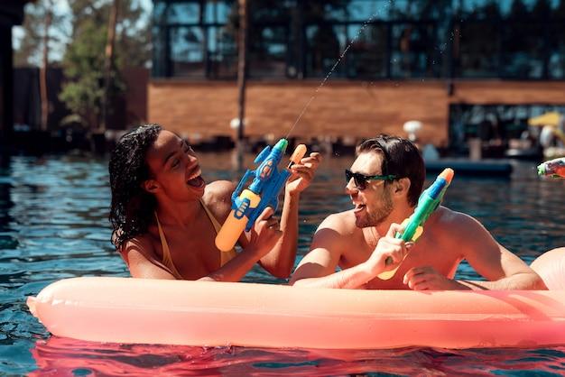 Junge glückliche menschen, die zusammen mit buntem wasser spielen