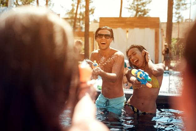 Junge glückliche menschen, die zusammen mit wasserwerfern spielen