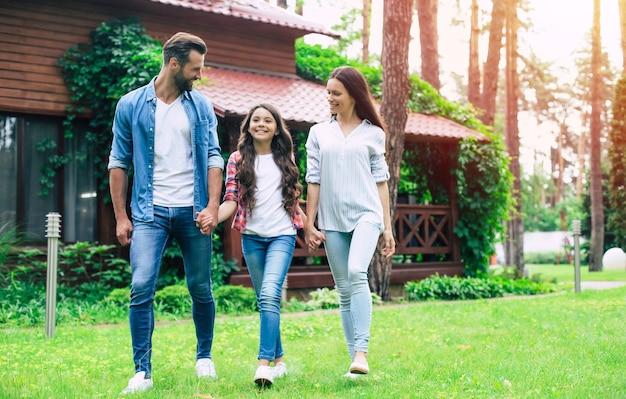 Junge glückliche moderne eltern mit einer niedlichen tochter gehen draußen