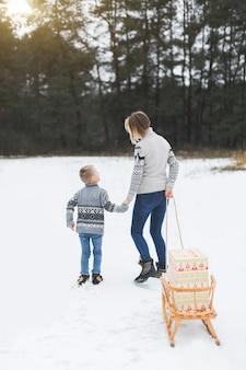 Junge glückliche mutter und ihr sohn genießen eine schlittenfahrt in einem schönen verschneiten winterwald