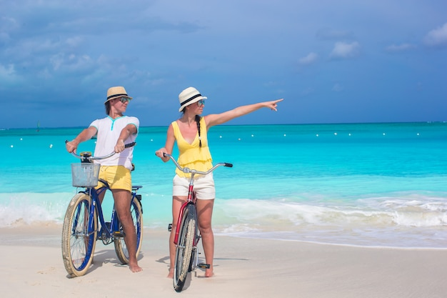 Junge glückliche paarreitfahrräder auf weißem tropischem strand