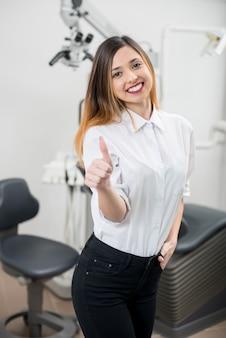 Junge glückliche patientin mit perfekten weißen zähnen, die daumen nach der behandlung an der modernen zahnklinik zeigen. konzept für zahnmedizin, medizin und gesundheitswesen.