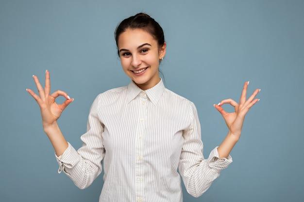 Junge glückliche positive attraktive brünette frau mit aufrichtigen gefühlen, die weißes hemd trägt