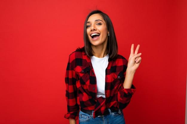 Junge glückliche positive coole schöne brünette frau mit aufrichtigen emotionen, die weißes t-shirt und stylisches rotes karohemd einzeln auf rotem hintergrund mit kopienraum trägt und zwei finger zeigt