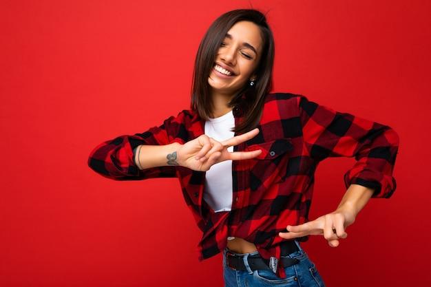 Junge glückliche positive entzückende gewinnende lächelnde nette kühle schöne brünette frau mit aufrichtigen gefühlen, die weißes t-shirt und stylisches rotes karohemd einzeln auf rotem hintergrund mit kopienraum trägt