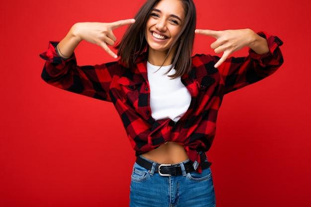 Junge glückliche positive lächelnde kühle attraktive brünette frau mit aufrichtigen gefühlen tragend