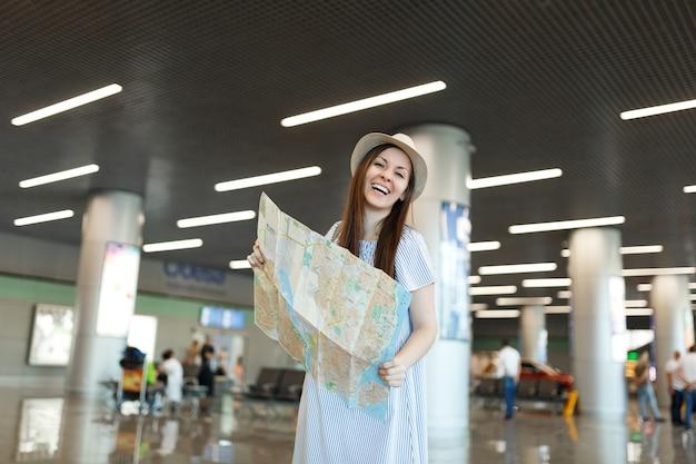 Junge glückliche reisende touristenfrau mit hut, die papierkarte hält, route sucht, während sie in der lobbyhalle am internationalen flughafen wartet?