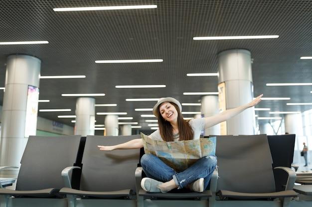 Junge glückliche reisende touristenfrau mit papierkarte sitzen mit gekreuzten beinen, die die hände wie im flug ausbreiten, warten in der lobbyhalle am flughafen