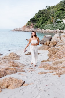 Junge glückliche ruhige kaukasische frau mit ukulele am tropischen felsigen strand bei sonnenuntergang