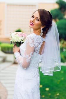 Junge glückliche schöne braut im weißen eleganten hochzeitskleid mit blumenstrauß, der draußen im park aufwirft.