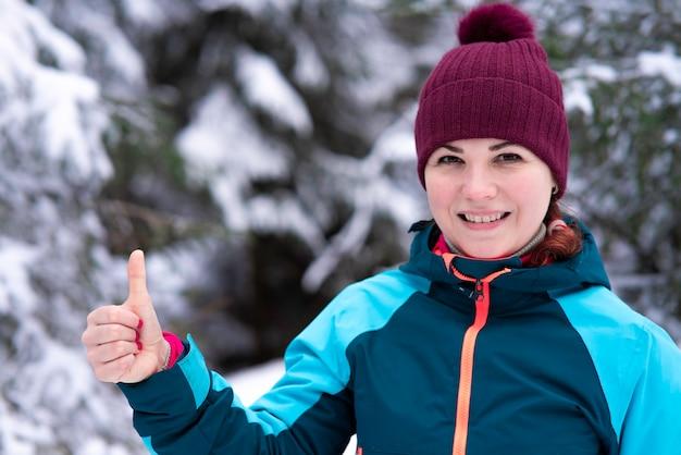 Junge glückliche schöne frau in der warmen kleidung und im hut steht in einem schneebedeckten winterwald