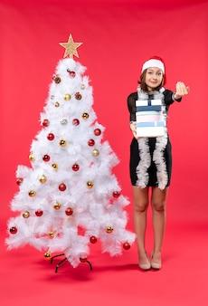 Junge glückliche schöne frau mit weihnachtsmannhut und stehend nahe dem geschmückten weihnachtsbaum, der geschenke hält und jemanden anruft