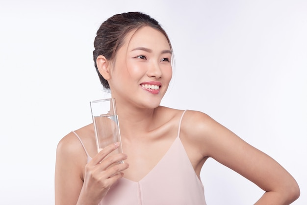 Junge glückliche schönheit gesunde asiatische frau, die glaswasser mit smileygesicht hält