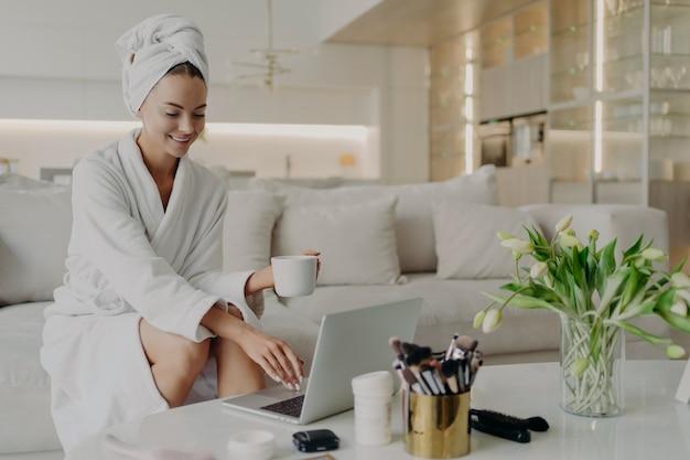 Junge glückliche schönheitsbloggerin in bademantel und handtuch auf dem kopf, die auf einem bequemen sofa im modernen wohnzimmer sitzt und am laptop arbeitet, tee trinkt und sich nach dem duschen zu hause entspannt fühlt