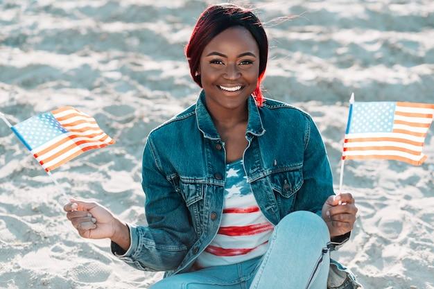 Junge glückliche schwarze frau mit amerikanischen flaggen