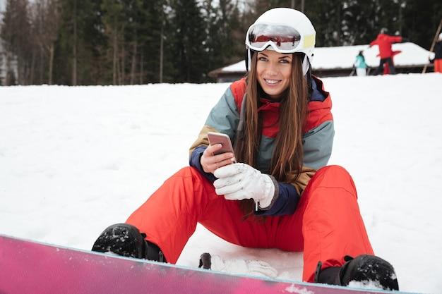 Junge glückliche snowboarderin liegt am frostigen wintertag auf der piste, während sie per telefon chattet