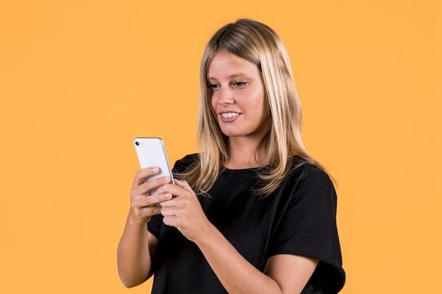 Junge glückliche sperrungsfrau, die handy auf gelbem hintergrund verwendet