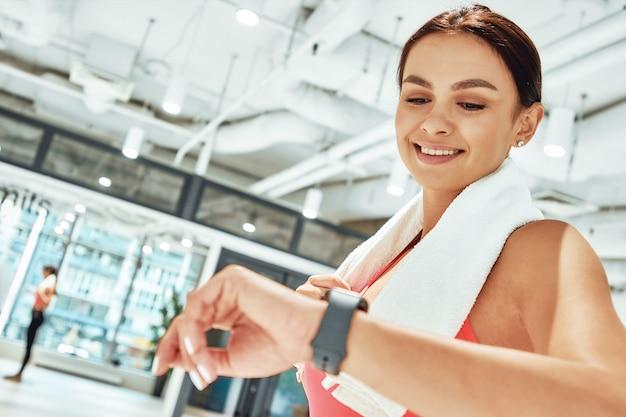 Junge glückliche sportliche frau mit weißem handtuch auf den schultern, die beim training auf smartwatch schaut