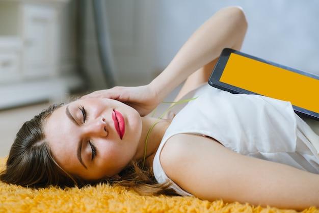 Junge glückliche studentin, die auf dem boden liegt und musik vom tablett drinnen zu hause hört